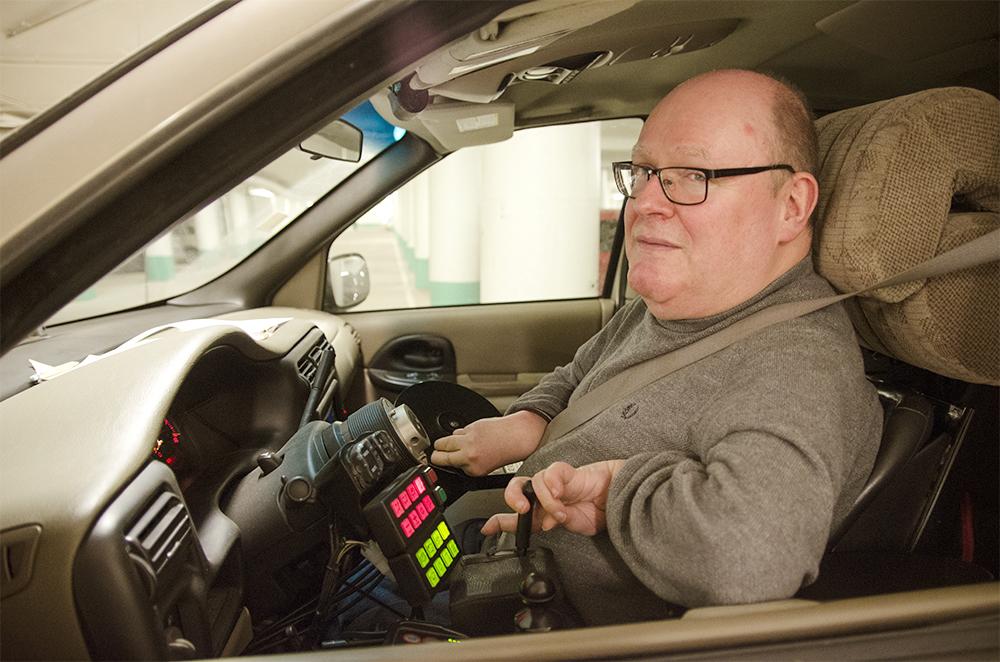 Man som sitter i förarsätet på sin bil, tittar in i kameran. Bilen är anpassad för att kunna köra även med begränsad rörelsefrihet.