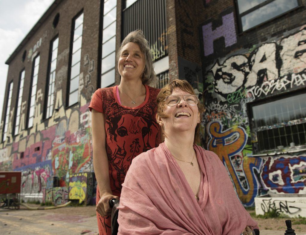 Kvinna i rullstol tittar upp mot himlen. Kvinna bakom tittar snett framåt. Båda ler. Bakom dem en graffitivägg.